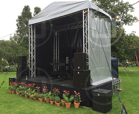 Small covered stage for private garden party.